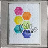 "This handmade card is great for any and every occasion as the stamped sentiment reads ""oh, hello there"" in black ink. It overlaps a colorful pattern of watercolored hexagons in a rainbow order. The card front has an awesome texture as it's been dry embossed with a hexagon pattern to coordinate with the stamped images. A thin black border outlines the perimeter of the card on the light grey card base."