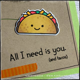 "An up-close, detailed view of the stamped, die-cut and colored taco on this handmade card. The stamped sentiment reads ""All I need is you. [and tacos]"" and is next to a strip of orange tone on tone striped washi tape. Hand drawn black lines surround the perimeter of the kraft card panel."