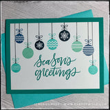 "This handmade holiday card features the main sentiment ""Season's greetings"" which is stamped in a dark turquoise color, coordinating with the card base. A variety of patterned ornaments hang from the top of the panel, surrounding the sentiment. The ornaments are stamped in shades of aqua, turquoise and navy blues, while hand drawn black strings reach to the top of the card panel as if they are really hanging. A turquoise envelope is included and layered beneath the card."