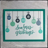 "A classic flat-lay of this handmade holiday card, the sentiment ""season's greetings"" is stamped in the center of the card front. The color coordinates with the color of the card base. A series of nine hanging ornaments graces the top portion of the card, cascading along the top. Shades of aquas, turquoises and deep blues evoke a wintery feeling."