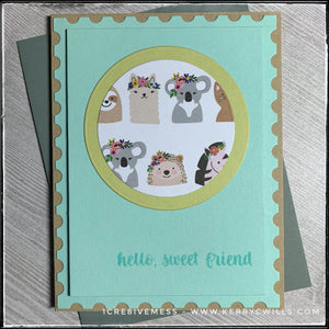 """hello, sweet friend"" is stamped in aqua ink on an aqua panel that's elevated off of the kraft card base. The border around the panel is designed to look like a postage stamp. Centered on the panel is a die-cut soft green circle that's layered with a smaller circle in a fun animal pattern. The animals all have flowery headdresses and are super cute. A grey envelope is shown as well and is included with this handmade friendship card."