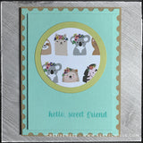 "A flat-lay view of this handmade friendship card. Decorative patterned paper with a slew of wildlife animals wearing flowery headdresses adorns a die-cut circle near the top center of the card panel. Designed to resemble a postage stamp, the edges of the panel have a scalloped detail and the center portion of the panel is elevated off of the card base for added dimension. The stamped sentiment reads ""hello, sweet friend"" and is stamped in aqua ink near the bottom right corner of the card."