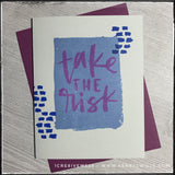 "This handmade card is of the encouragement type, with the big bold message ""take the risk"" stamped in purple ink over a watercolor-esque rectangle on the light grey card front. Small darker blue dashed lines accent the sides of the rectangle. A deep purple envelope is included and is shown layered under the card."