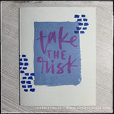 "A flat-lay view of this encouraging handmade card, the message stamped front and center reads ""take the risk"" in purple ink. The sentiment is layered over a blue rectangle on the middle of the soft grey card base. Small dark blue dashed lines surround the sentiment on either side."