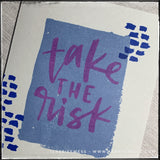 "An up-close, angled view of the main elements on the front of this handmade card. A blue rectangle that appears to have a watercolored finish creates a nice bold background for the stamped sentiment ""take the risk."" Smaller, darker blue dashed lines accent the sentiment on either side."