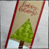 "This angled flat-lay view includes the sentiment ""happy holidays"" in red ink, in a scripty font. The red color coordinates with the color of the slimline card base. The faux-stitched detail is visible around the edges of the card panel, the tree, tree trunk and snowbank. Inked patterns add dimension and detail."