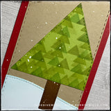 An angled flat-lay of the card front, focusing on the detail on the holiday tree created from a die-cut triangle, stenciled with overlapping smaller triangles in shades of green ink. The edges of the tree and the tree trunk coordinate with the edges of the card front panel - all with faux stitched detail.