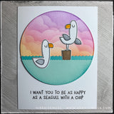 "Die-cut elements including a main circular focal point, splashing waves and two sassy seagulls fill the front of this handmade card. Portions of the background have been ink blended creating a cloud filled scene and the seagulls have been hand colored. The sentiment reads ""I want you to be as happy as a seagull with a chip"" and is stamped in black ink."