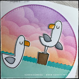 A detailed view of the die-cut details on the front of this handmade card. Two seagulls are facing each other, one on a wooden piling and one floating in the water. The sky has been blended with a cloud stencil and various shades of colors create a calming sunset.