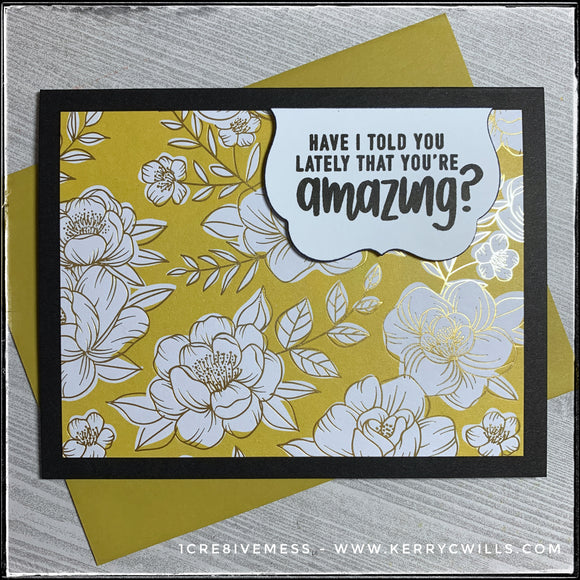 This handmade card has a complimentary sentiment and features a regal color scheme, complete with gold accents. A black card base holds a panel of decorative patterned paper in a floral pattern with gold accents. A small white scalloped die-cut is elevated off of the card base and houses the sentiment