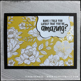 "This handmade card has a complimentary sentiment and features a regal color scheme, complete with gold accents. A black card base holds a panel of decorative patterned paper in a floral pattern with gold accents. A small white scalloped die-cut is elevated off of the card base and houses the sentiment ""Have I told you lately that you're amazing?"" which is stamped in black ink. The color of the card panel is a combination of citrine and topaz and has a true jewel tone to it."