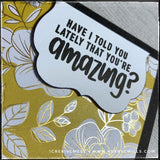 "An angled view of the sentiment on the die-cut which reads ""Have I told you lately that you're amazing?"" and is stamped in black ink. The die-cut is elevated off of the card base with foam tape for added dimension. The gold accents on the patterned paper glisten and shine when the light is reflected against it. There's a gorgeous floral pattern with a warm jewel toned color against a bold black card base."