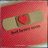 "An up-close, angled view of the details on this handmade card front. The image of a bandaid has been die-cut from fun foam with three separate layers. The sentiment stamped below the bandaid reads ""feel better soon"" in black ink. The decorative dots on the sides of the bandaid coordinate with the dots on the background patterned paper which is red with tone-on-tone dots."