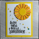 "A complimentary style handmade card, this is full of bright colors and sunshine - literally! The sentiment ""You are my sunshine"" is stamped in black ink near the bottom of the front card panel. A die-cut sun is layered with two colors of fun foam for added dimension and is accented by a smattering of colorful, shiny sequins."