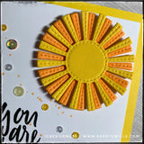 A head on view of the die-cut sunshine, layered in two colors - light orange and bright yellow. There's a faux-stitched detail on the rays and they are elevated off of the card base. It's such a happy element that's sure to make your recipient smile!
