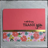 "A floral patterned thank you card with gold accents, this handmade card will show your appreciation in style! The stamped sentiment reads ""a note to say thank you"" in black ink near the right side of this horizontally oriented card. A thin strip of shiny metallic gold specialty cardstock divides the sentiment from the rectangular block of floral patterned paper. The coral colored card base coordinates with the flowers on the patterned block. The teal flowers accent the included envelope. The upper left corn"