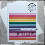 "A colorful handmade birthday card, ideal for helping them celebrate! A white card base lays the groundwork for a block of patterned paper which features a rainbow of horizontal stripes with thin white lines dividing between them. The words ""happy birthday"" are stamped in black about 2/3 down the block in black ink. Near the top right corner is a circle of white paper with a black linear design of floral images. The same pattern continues on a thin strip extending from the right side above the sentiment. A w"