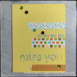 "A flat lay view of this handmade ""miss you"" style card. Strips of patterned paper accent the die-cut letters that spell out ""miss you"" and are accented by a smattering of sequins. The letter ""u"" is the same color as the card base, to play off of the sentiment - missing you."
