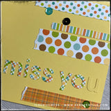 "An up-close, detailed view of the patterns and sequins on the front of this handmade card. Colorful strips of patterned paper have a purposely torn edge and surround the die-cut word ""miss you."" Patterns include polka dots, stripes and plaids. A smattering of sequins spans across the card front as well for a slightly dimensional addition."