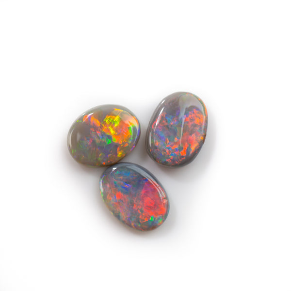Loose Lightning Ridge black opal stones. Three oval cut opals totalling 2.5ct. Showing full spectrum of colour. Buy today at Tamahra Prowse.