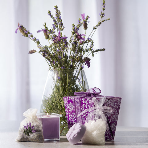 Purple lavender take out box with much of lavender salts, small lavender candle, pouch of lavender seeds, small round flower lavender soap
