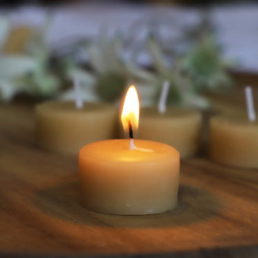 Collombatti Naturals Candle Burning Tips Blog - A Collombatti Naturals Beeswax Tealight Candle burning on a wooden bench top with unlit candles behind it