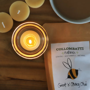 Collombatti Naturals Candle Burning Tips Blog Lit Collombatti Naturals tealight candle in a glass tealight holder with a packet of Collombatti Naturals Sweet'nSticky chai beside the candle and a mug of chai behind the candle.
