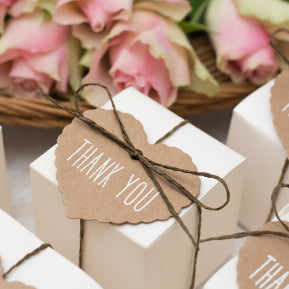 Collombatti Naturals step by step guide to the best eco friendly gift boxes blog white boxes tied in eco brown twine with a brown paper heart that says thank you with pink roses in the background