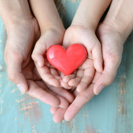 Collombatti Naturals step by step guide to the best eco friendly gift boxes blog - a child's hands being held by a parents holding a red heart