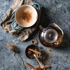 Collombatti Naturals - 8 reasons to love tea this winter blog - a two handle pot of chai sitting on a tea towel with a glass teapot and spices scattered around