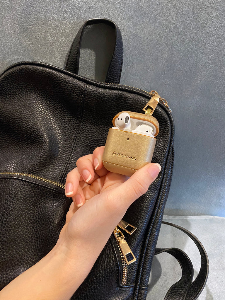 Mixed Metals AirPods Case clipped with metal clasp to a backpack