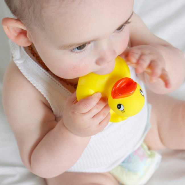 A baby is chewing on Playgro rubber duckie on the bath tub