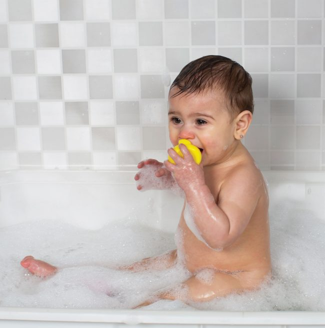 A baby boy on the bath tub playing with Playgro yellow color Rubber duckie in his mouth