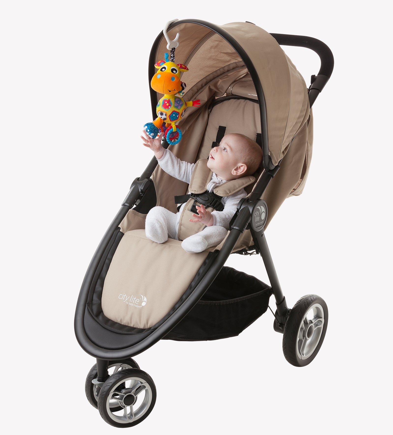 A baby in a stroller trying to reach Playgro Giraffe Stroller toys hanging in  the stroller canopy