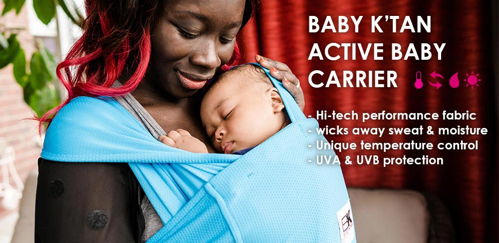 A Mother holding her baby in Blue Baby K'tan Active Carrier at Not Too Big Store
