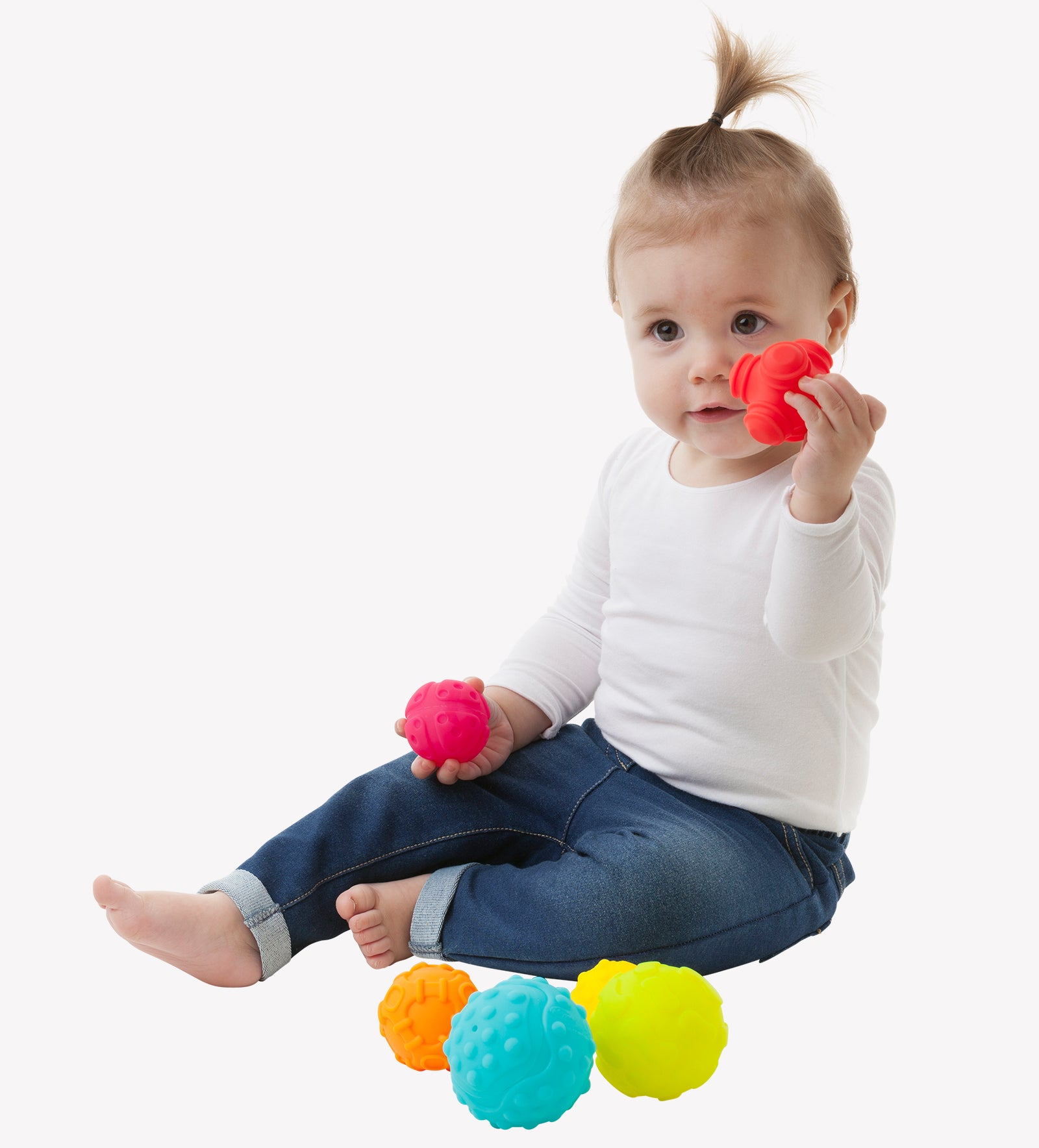 A toddler girl sits down on the floor playing colorful Playgro Textured Ball while holding the red ball