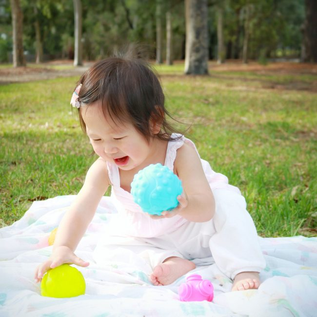 A toddler girl is playing with Playgro textured ball toys outdoor on the garden