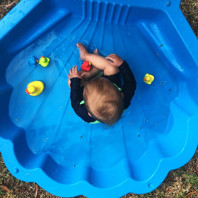 A toddler boy is playing Playgro Colorful Rubber duckie on the outdoor pool
