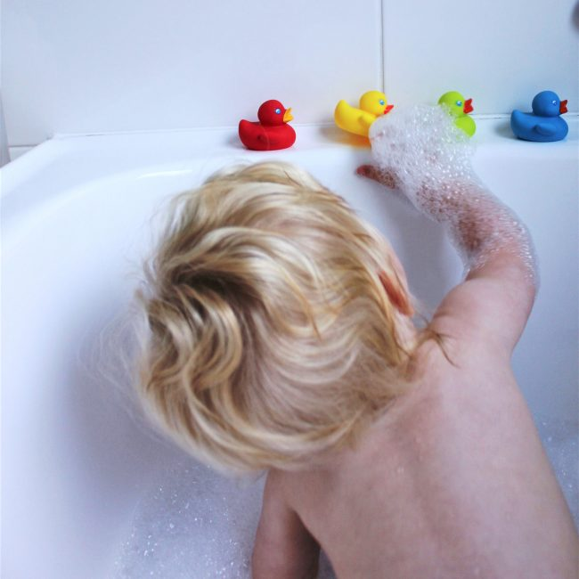 A toddler boy on the bubble buth tub is reaching out to Playgro colorful rubber duckie