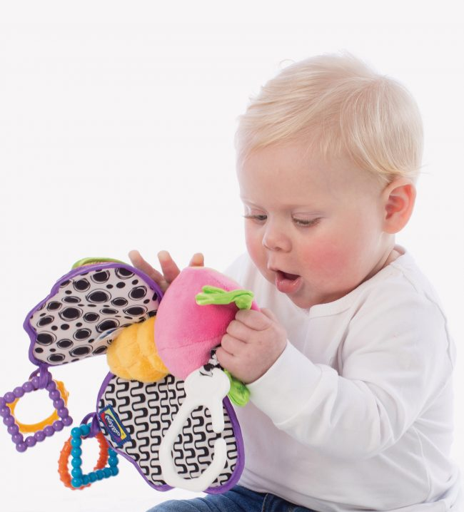 A baby boy play with a teether activity baby toy