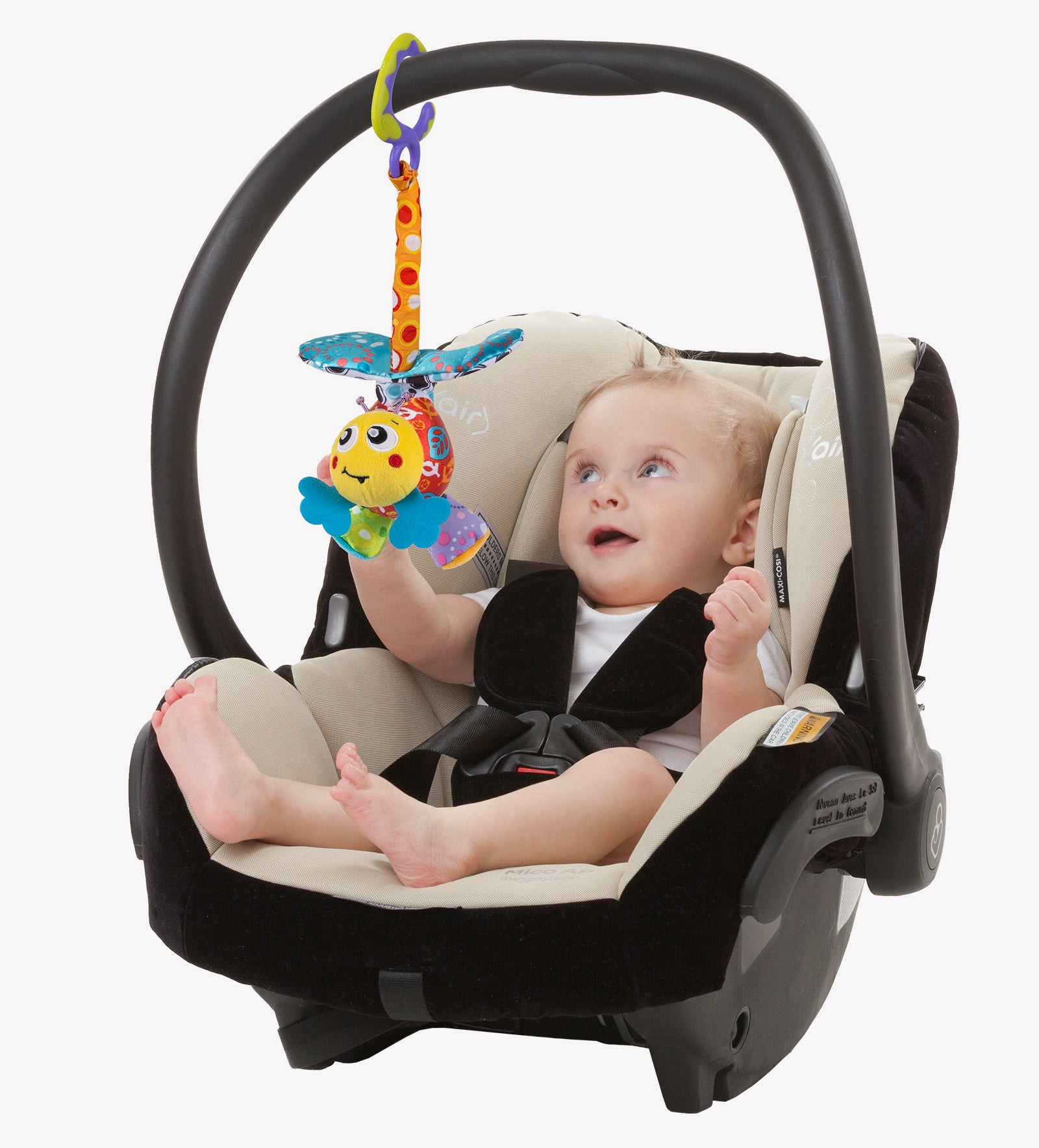 A baby boy is sitting inside a car seat with Playgro Mover Bee baby toy clipped on to it.