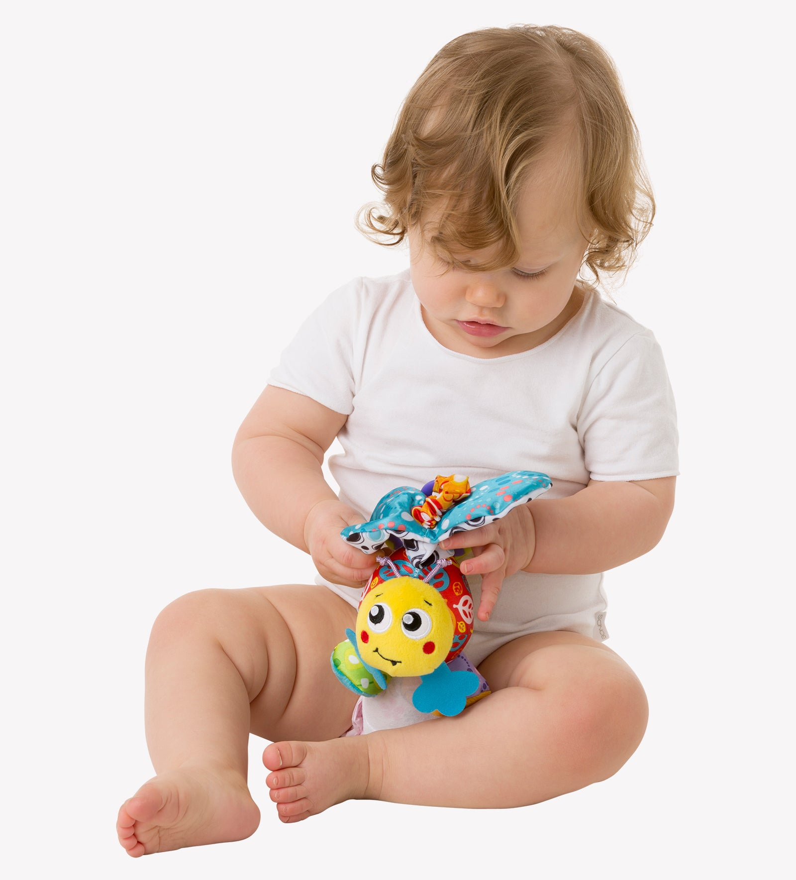 A toddler boy is playing with his Playgro Plush toy mover bee in his lap