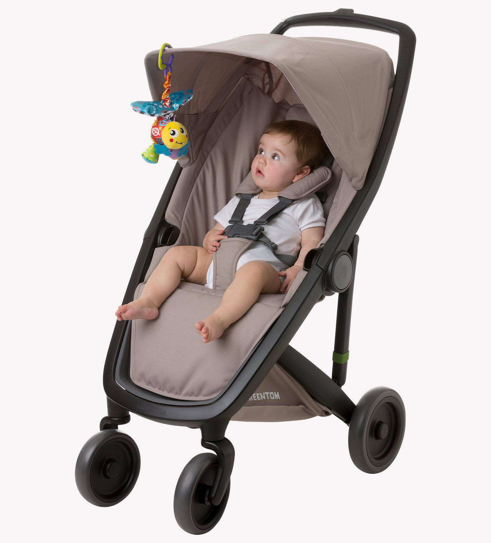 A toddler boy sitting on the stroller with Playgro stroller toy attached on the stroller canopy