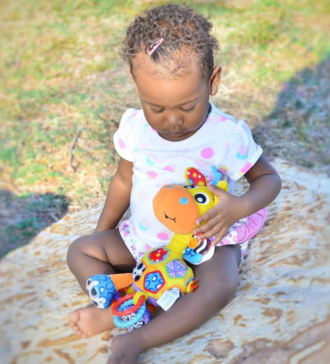 A toddler is sitting outdoor on the rocks holding Playgro Giraffe baby toys in her lap bought from Not Too Big Online Store