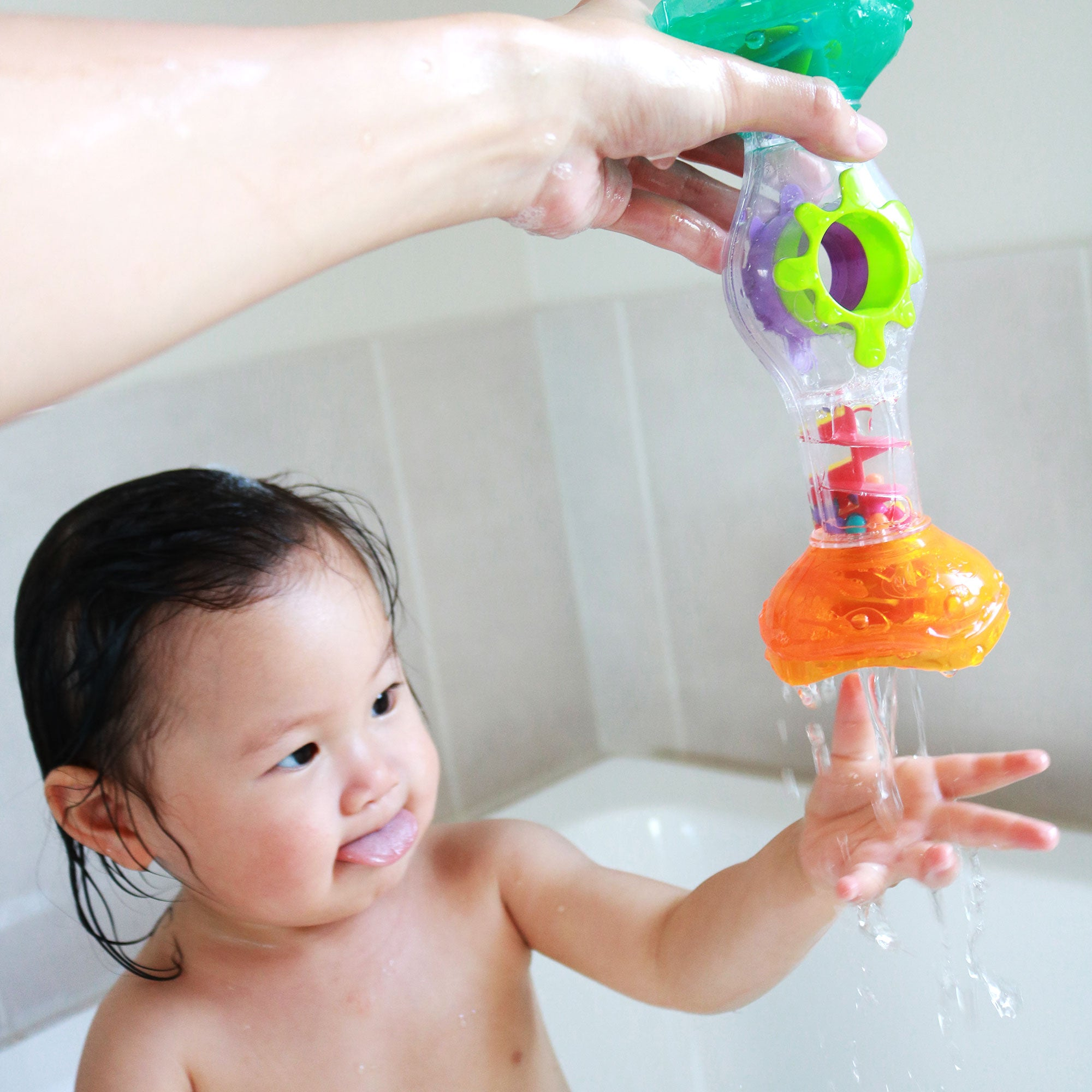 A toddler girl plays Playgro Rainmaker toy with her mum in the waterplay