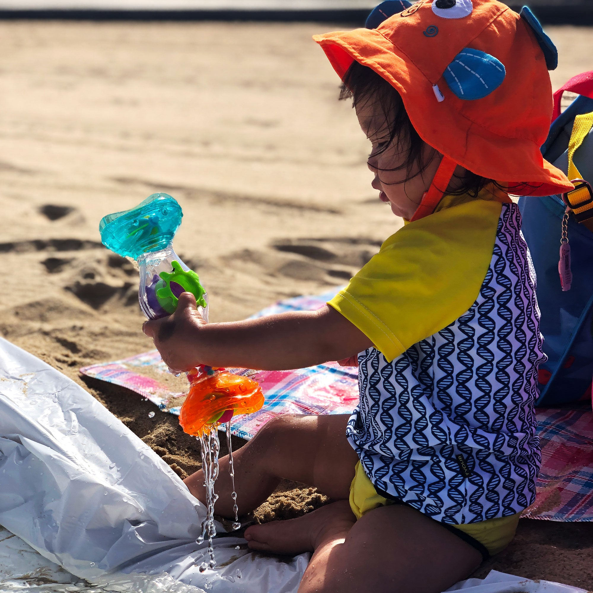 a toddler girl in the beach is playing with Playgro Rainmaker toys
