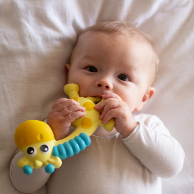 A baby lying down in bed chewing on Playgro Jerry baby teether