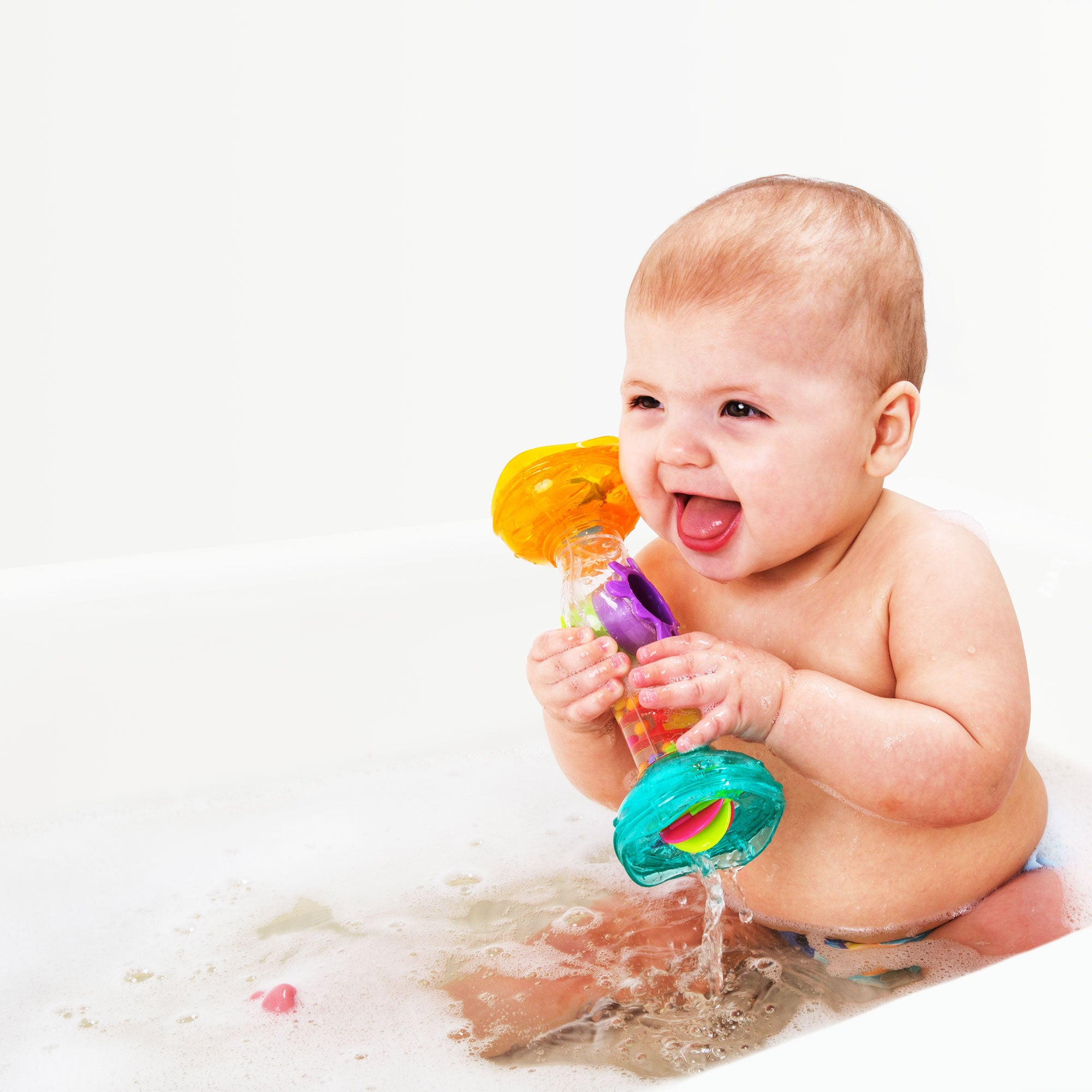 A baby boy playing Playgro rainmaker toy in the bath tub