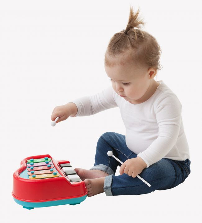 A toddler boy is playing with Playgro Xylophone musical toys while sitting on the floor