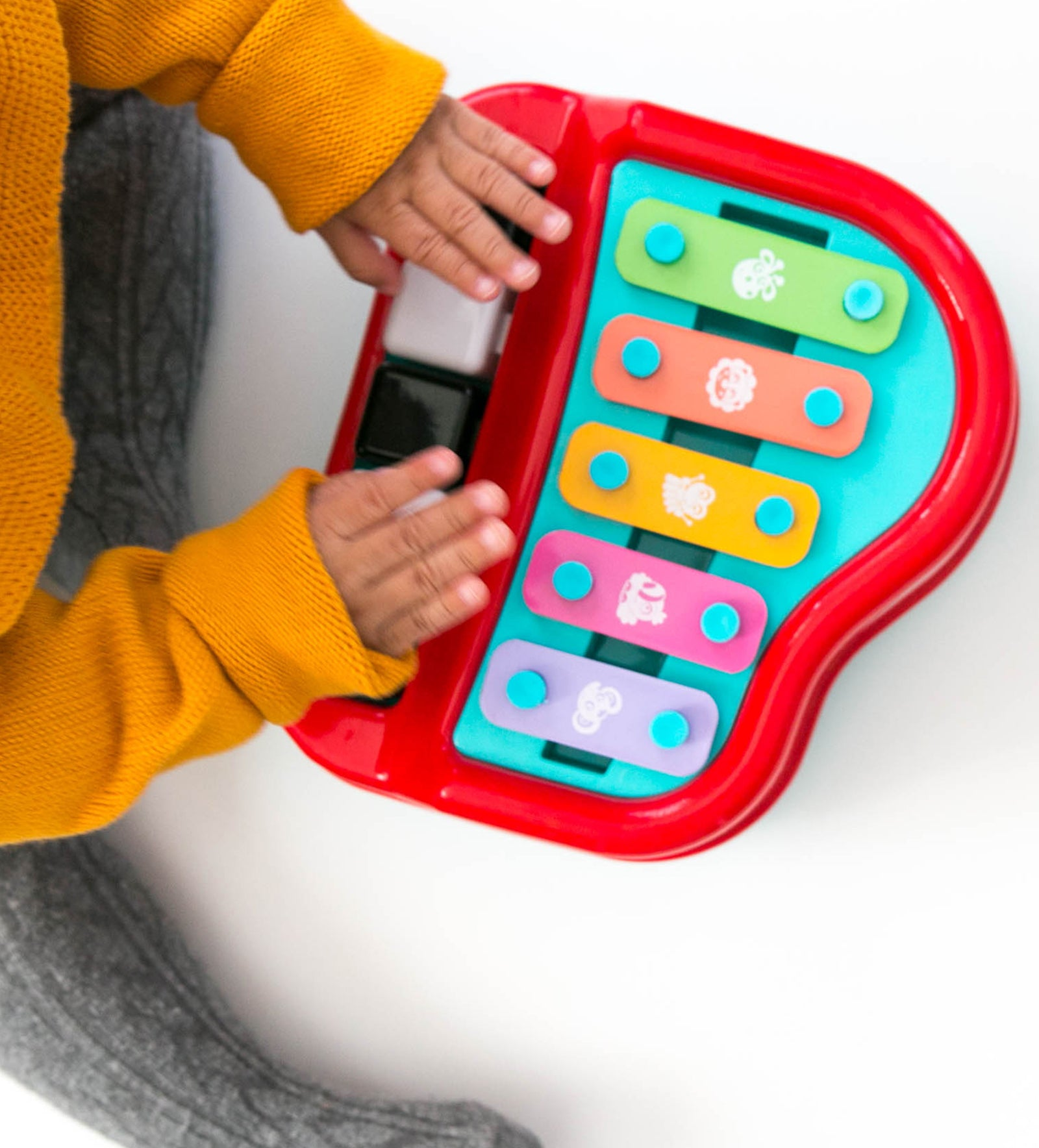 A toddler's hand wearing mustard color long sleeve is playing the Playgro Xylophone musical toy
